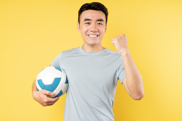 勝利の表情でボールを保持しているアジア人男性