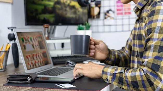 Азиатский мужчина держит кредитную карту для покупок в интернете с портативным компьютером и вводит код безопасности