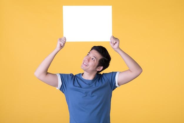 노란색 배경에 고립 된 빈 빈 보드를 들고 아시아 남자