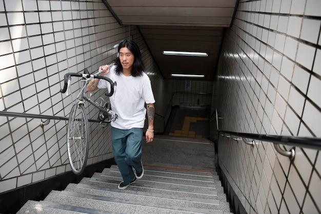 Азиатский мужчина держит велосипед