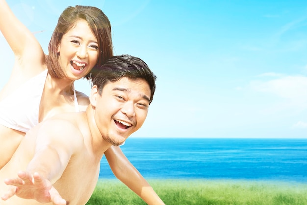 Asian man holding his girlfriend in a bikini on the field with ocean view