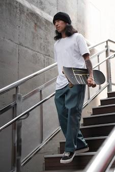 階段を歩きながらスケートボードを持っているアジア人男性