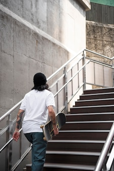 Asian man holding his skateboard while walking on the stairs