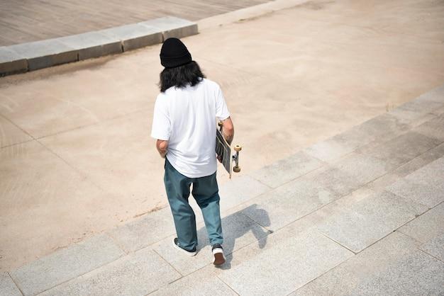 彼のスケートボードを保持しているアジア人男性
