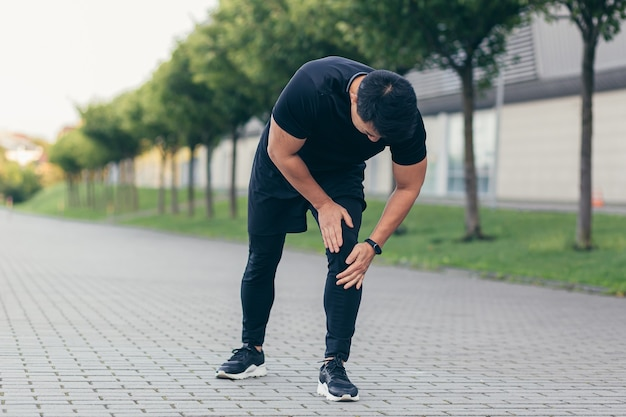 Asian man holding knee pain after running and fitness, severe leg pain