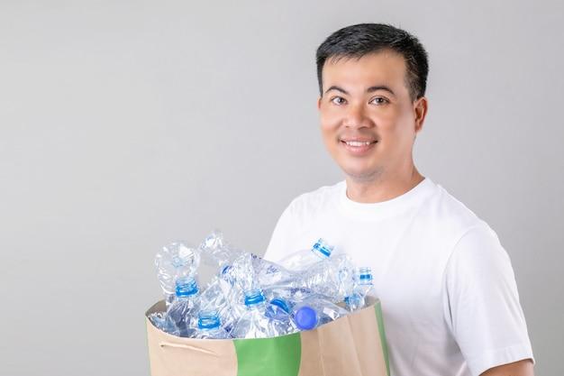 多くの空の澄んだ水のボトルを保持しているアジア人男性