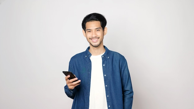 Asian man holding mobile phone smiling and looking at camera