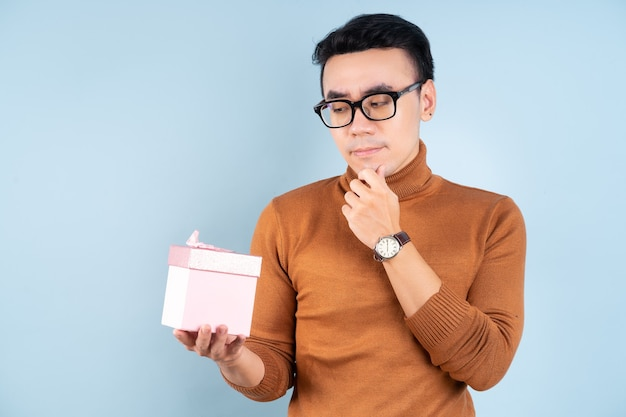Asian man holding pink giftbox on blue background