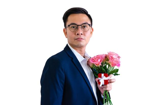 Азиатский мужчина держит розовые розы и подарочную коробку для концепции дня святого валентина.