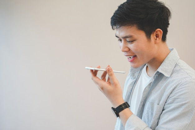 Asian man holding smartphone and talking by use voice control function for call with others