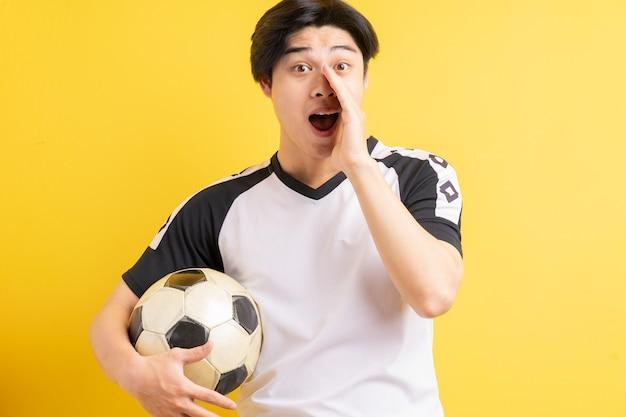 ボールを持って叫んでいるアジア人男性