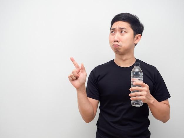 물병을 들고 복사 공간에서 슬픈 감정 포인트 손가락을 느끼는 아시아 남자