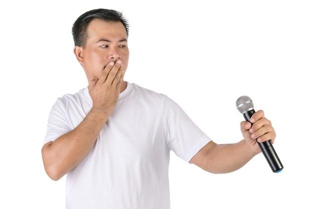 Азиатский мужчина держит беспроводной микрофон и не говорит