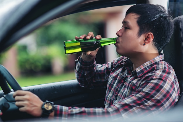 Азиатский мужчина держит бутылку пива в то время как за рулем автомобиля