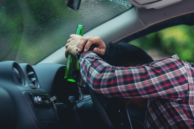 Asian man holds a beer bottle while is driving a car