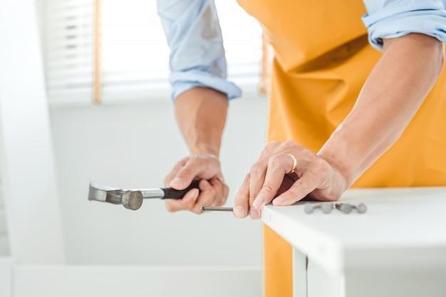 アジアの男性の家の改善家具の組み立て説明書を読み、ハンマーを使って釘を木に突き刺します。