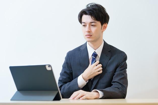 온라인 인터뷰에 참석하거나 긴장된 표정으로 회의에 참석하는 양복을 입은 아시아 남자