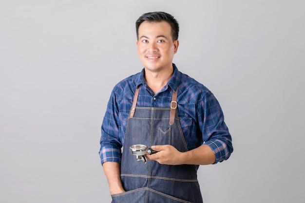 Азиатский мужчина в форме бариста, держащий кофемашину