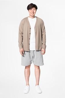 Азиатский мужчина в коричневом кардигане и шортах, удобной домашней одежде на все тело
