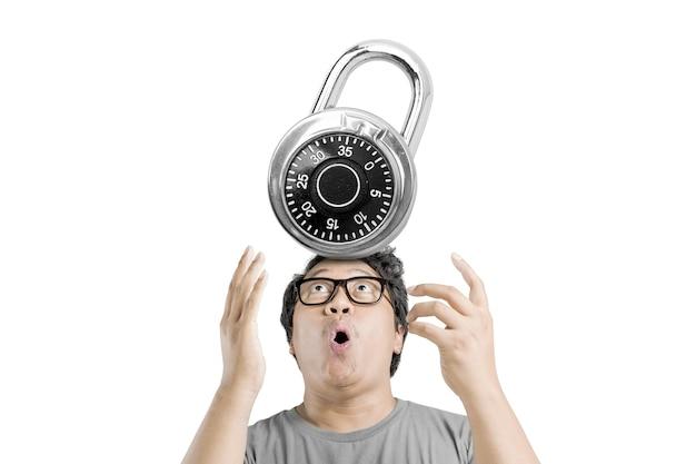白い背景の上に分離された南京錠によって押された興奮した表情を持つ眼鏡のアジア人男性