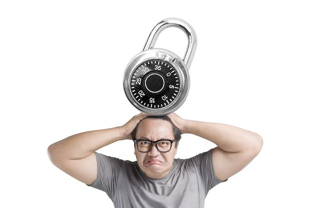白い背景の上に分離された南京錠によって押された不幸な表情を持つ眼鏡のアジア人男性