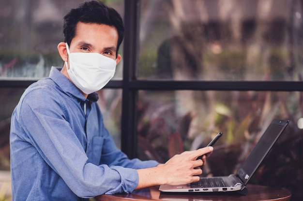 Азиатский мужчина в маске работает в офисе, работает над новым нормальным социальным дистанцированием