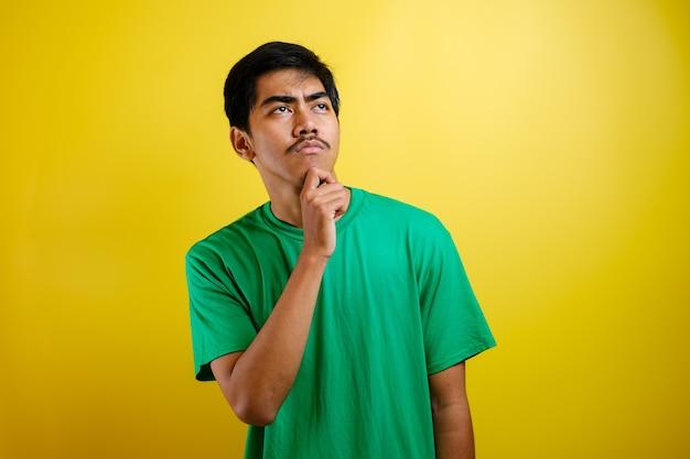 Азиатский мужчина в зеленой футболке что-то думает, ищет хорошую идею на желтом фоне