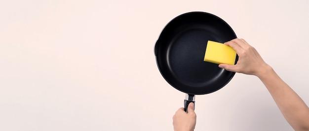 灰色のアジア人男性tシャツは、調理後の衛生のために柔らかい面が黄色で硬い面が緑色の便利な食器洗いスポンジでノンスティックパンを掃除します