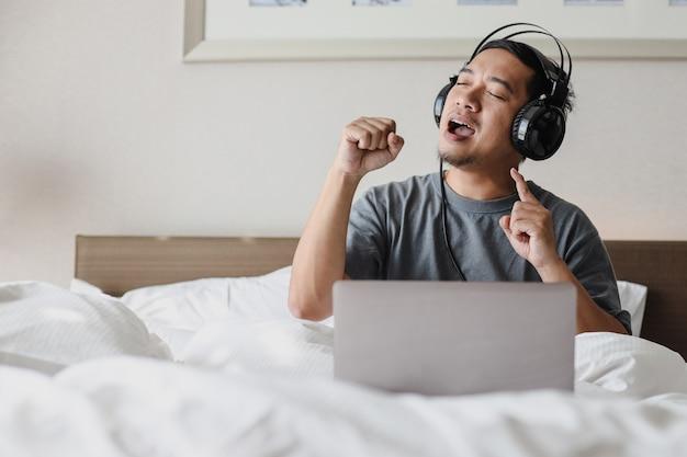 헤드폰을 끼고 침대에서 노래하는 동안 노트북에서 노래를 듣는 아시아 남자