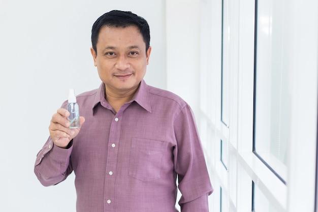 분홍색 셔츠를 입은 아시아 남자는 흰색 배경에 알코올 스프레이 병을 들고 있습니다.