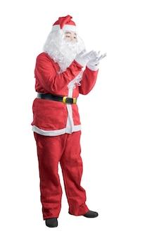 サンタの衣装を着たアジア人男性が白い背景で隔離の彼の手に何かを吹く