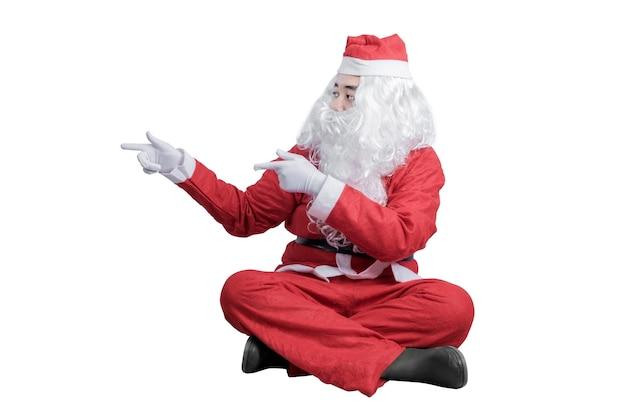 흰색 배경 위에 절연 뭔가 가리키는 산타 의상에서 아시아 남자. 복사 공간을위한 공간