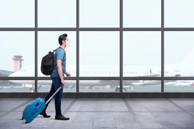Азиатский мужчина в маске с рюкзаком и чемоданом на аэровокзале. путешествие в новой норме