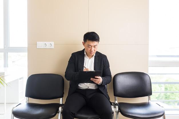 Азиатский мужчина в зале ожидания сидит на стуле возле рецепции офисного центра