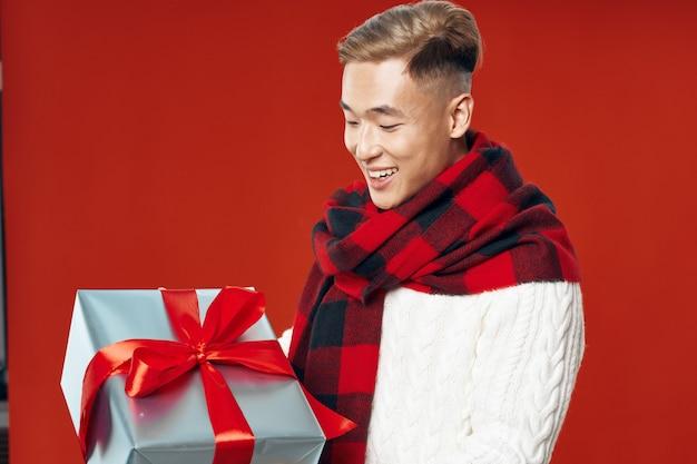Азиатский мужчина в теплой зимней одежде позирует пространство на цветном пространстве