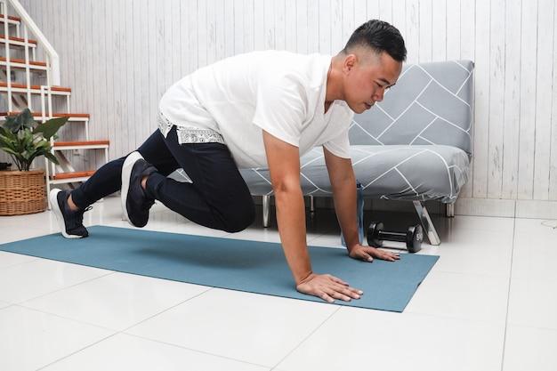 Азиатский мужчина в белой рубашке на синем коврике делает упражнения и разминается