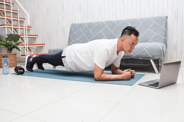 Азиатский мужчина в белой рубашке на синем коврике делает планку во время просмотра видео-урока фитнеса на ноутбуке