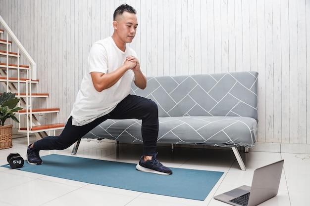 Азиатский мужчина в белой рубашке на синем коврике разминается на растяжке и смотрит видеоурок по фитнесу онлайн на
