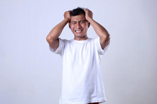흰색 배경에 짜증나고 화난 표정으로 흰 셔츠를 입은 아시아 남자