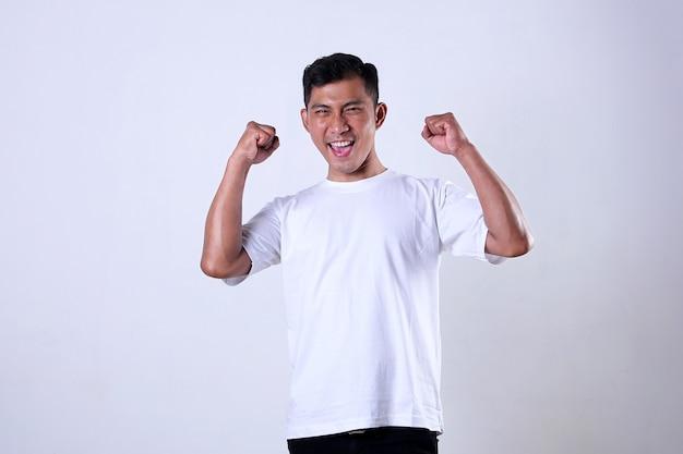 Азиатский мужчина в белой рубашке с выражением празднует победу изолированного на белом фоне