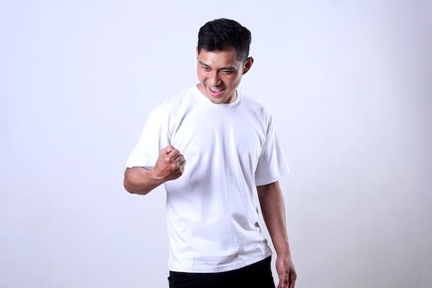 Азиатский мужчина в белой рубашке с счастливым выражением лица и взволнован до победы