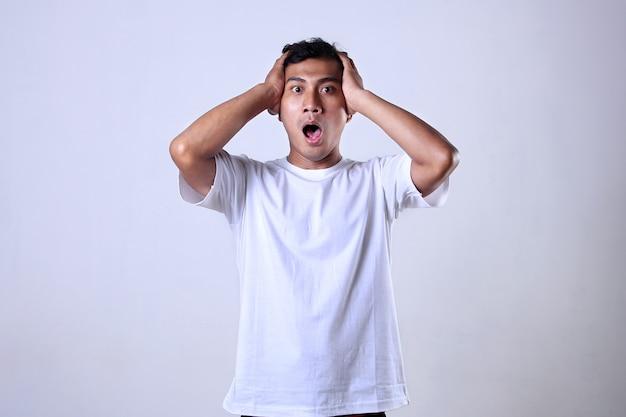 驚きと混乱した表情で白いシャツのアジア人男性白い背景で隔離