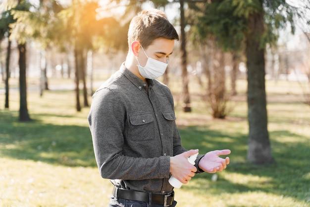 Азиатский мужчина в белой стерильной медицинской маске распыляет антисептик на руку