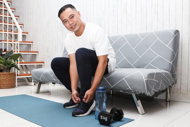スニーカーを結ぶ白いtシャツのアジア人男性が自宅で運動の準備をします