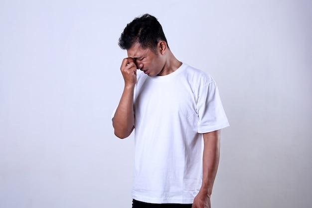 白い背景に分離された額を保持している表情と白いtシャツのアジア人男性