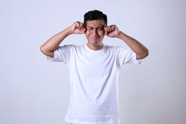 흰색 배경에 고립 된 재미있는 우는 표정으로 흰색 티셔츠를 입은 아시아 남자