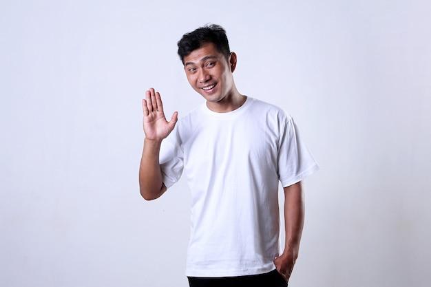 白い背景で隔離の挨拶表現と白いtシャツのアジア人男性