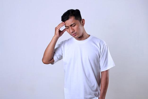 Азиатский мужчина в белой футболке с выражением головной боли изолирован на белом фоне