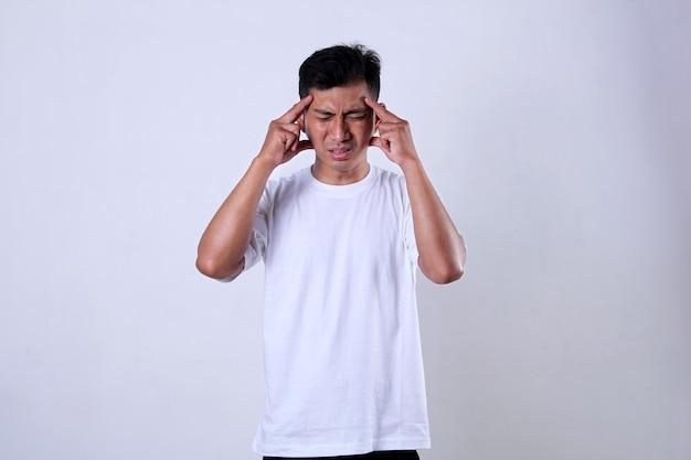 頭痛の表現と白いtシャツのアジア人男性白い背景で隔離