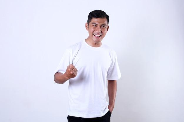 Азиатский мужчина в белом с торжествующим и счастливым выражением лица изолирован на белом фоне